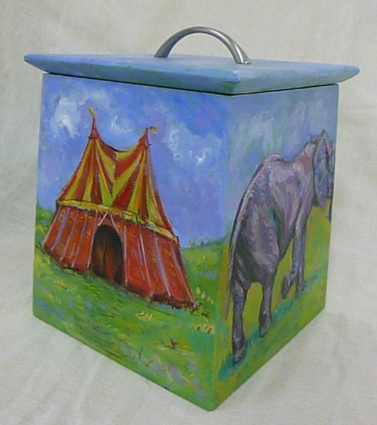 SHOPPING : A painted wood biscuit box with a lid by artist Zoe Cameron of a circus elephant walking passed a tent on green grass with blue sky
