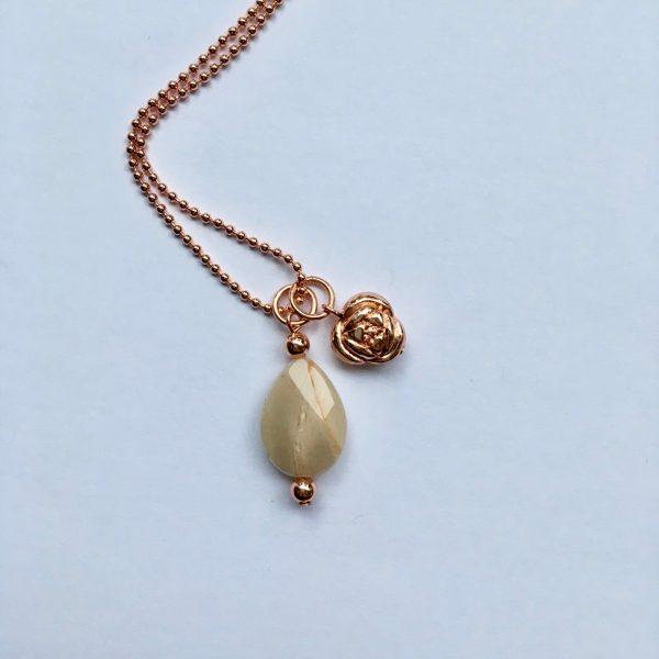 Lange edelsteen ketting met beige natuursteen druppel bloem bedel rosé goud