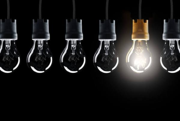 Light bulbs in row with single one shinning, isolated on black