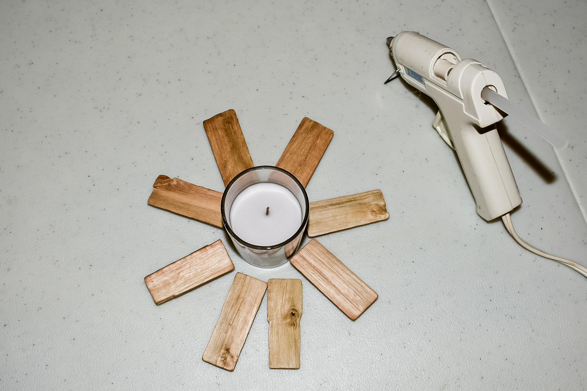 arranging wood slices around a votive candle to create diy woodland candles