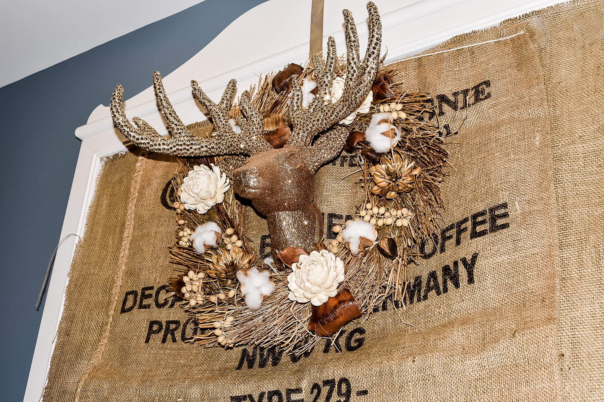gold deer head inside a neutral wreath mounted on a mirror covered with a burlap coffee sack