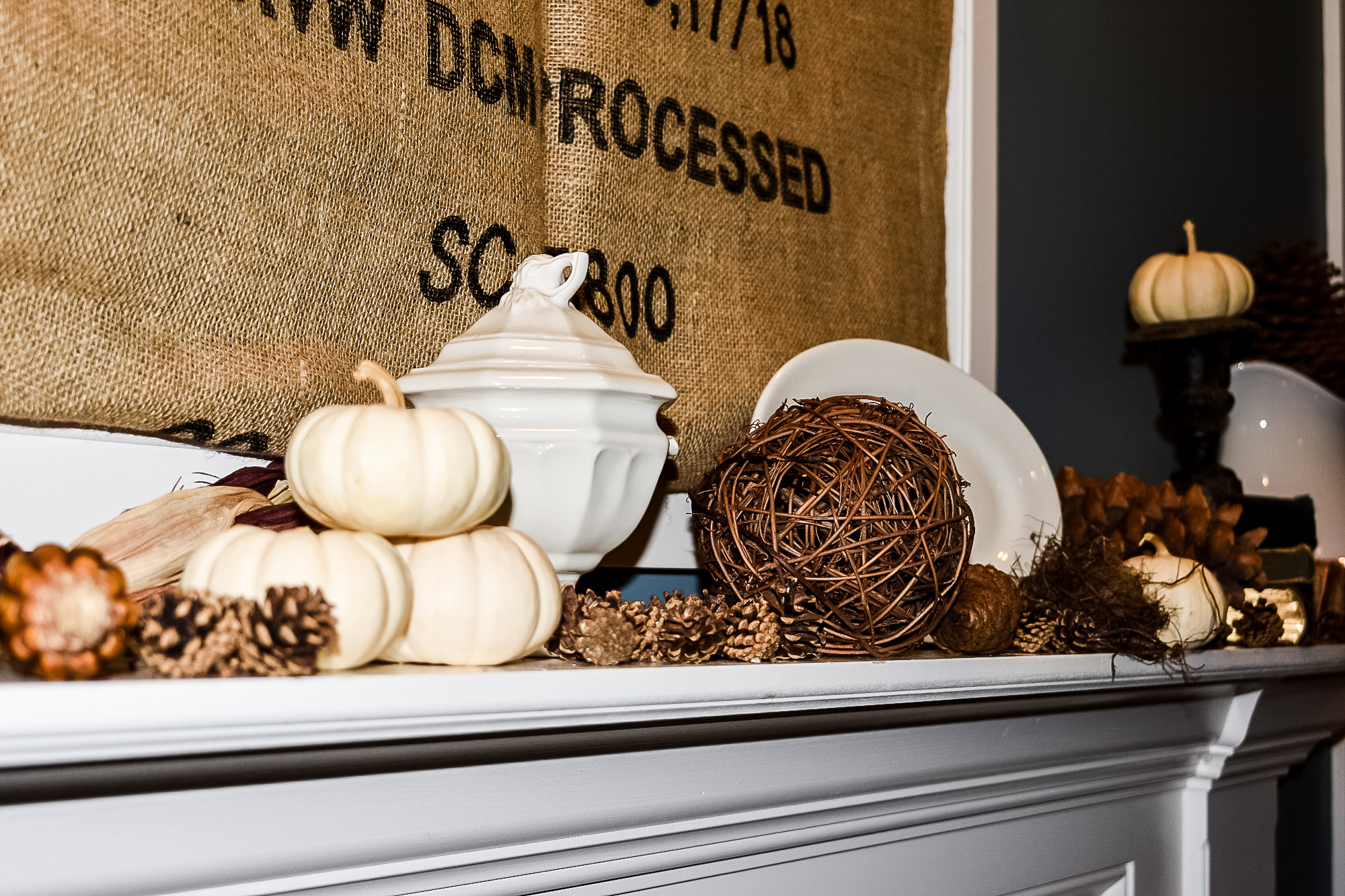 pumpkins, pinecones, ironstone, and a grapevine orb on a neutral fall mantel