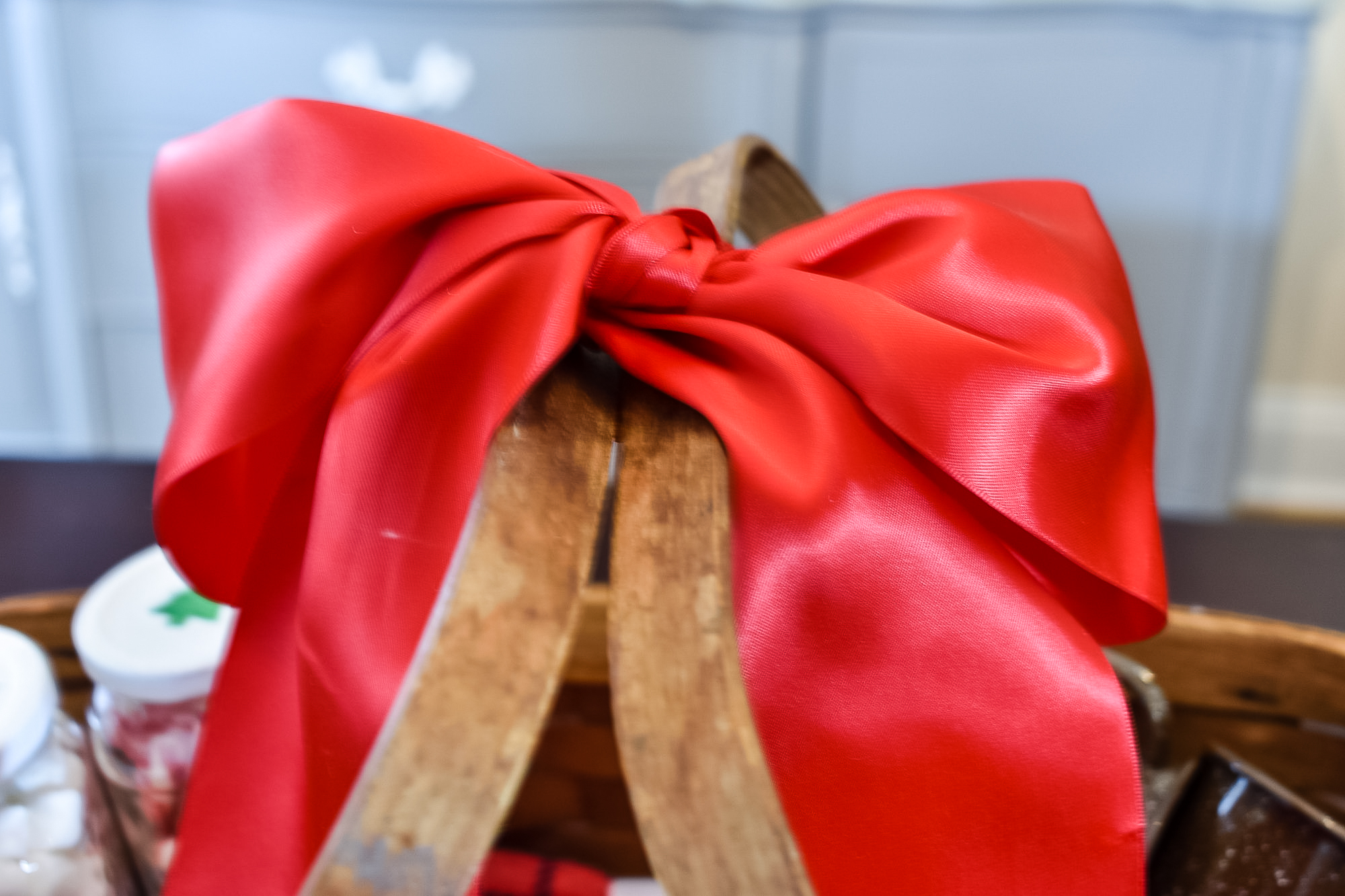 big red bow tied to the handles of a hot cocoa gift basket