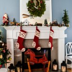 White Christmas mantel decorated with evergreens, pinecones, a vintage Santa, red stockings, a rocking horse and lanterns on the hearth