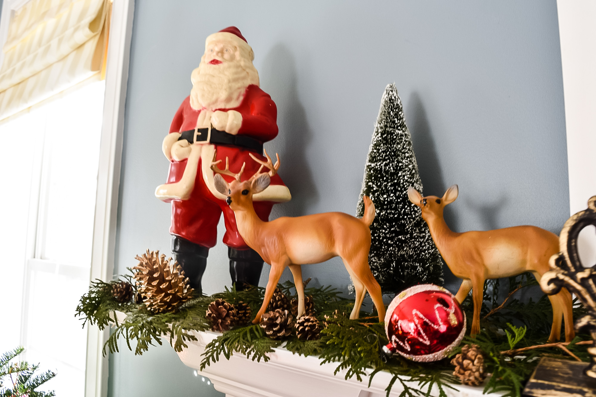 plastic vintage Santa and reindeer on a Christmas mantell