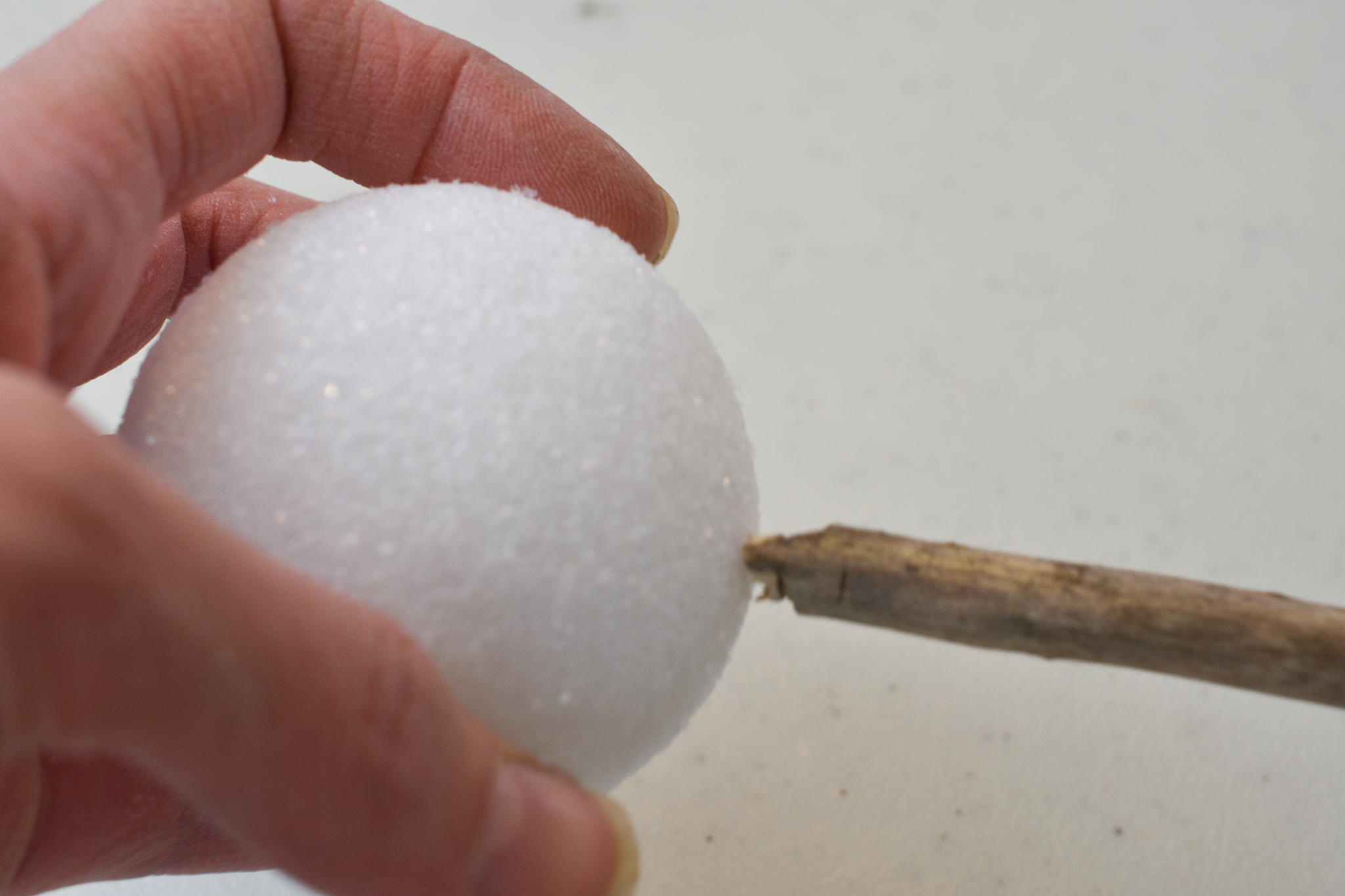 poking a hole in a foam ball with a twig