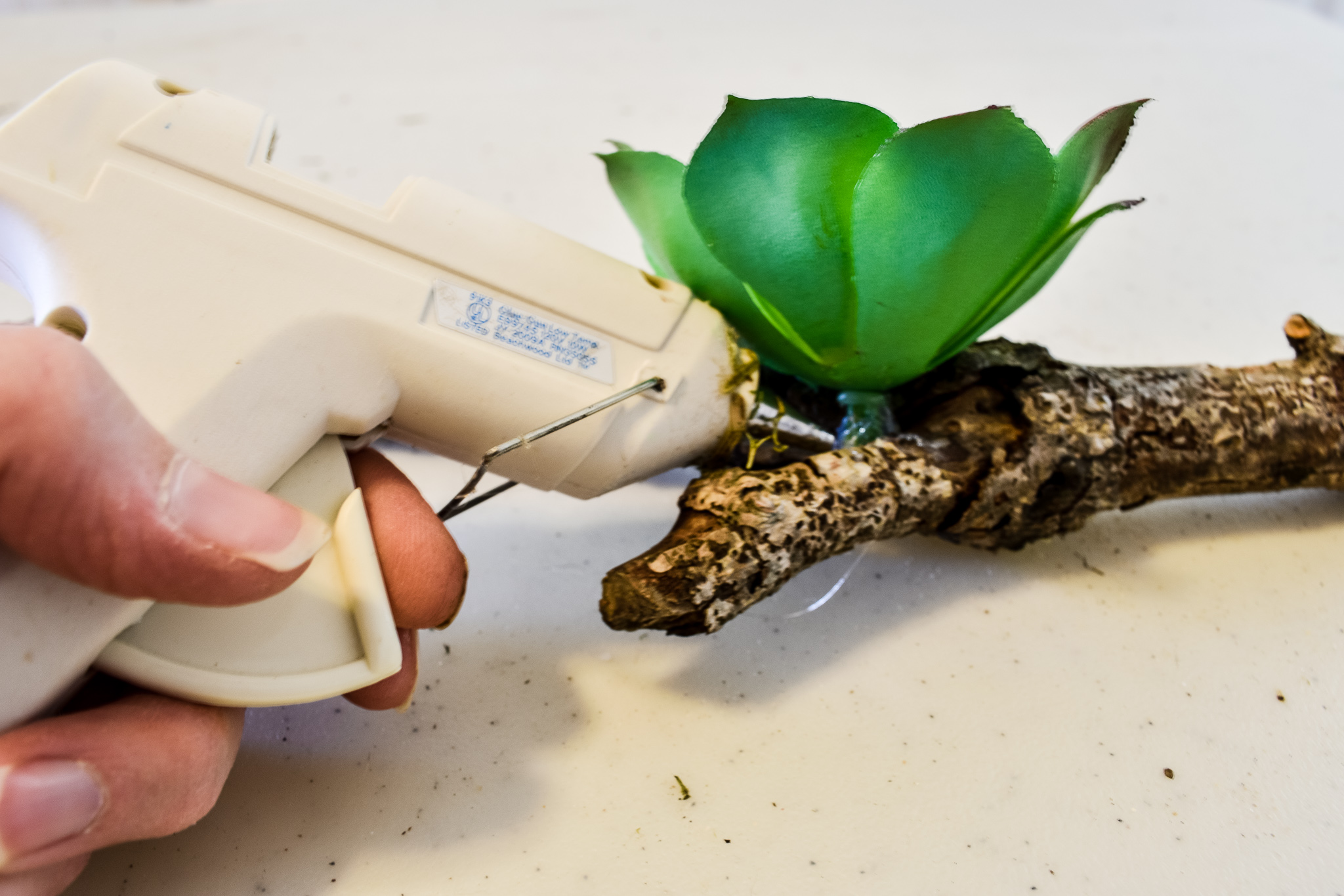 attaching a faux succulent to a twig with hot glue