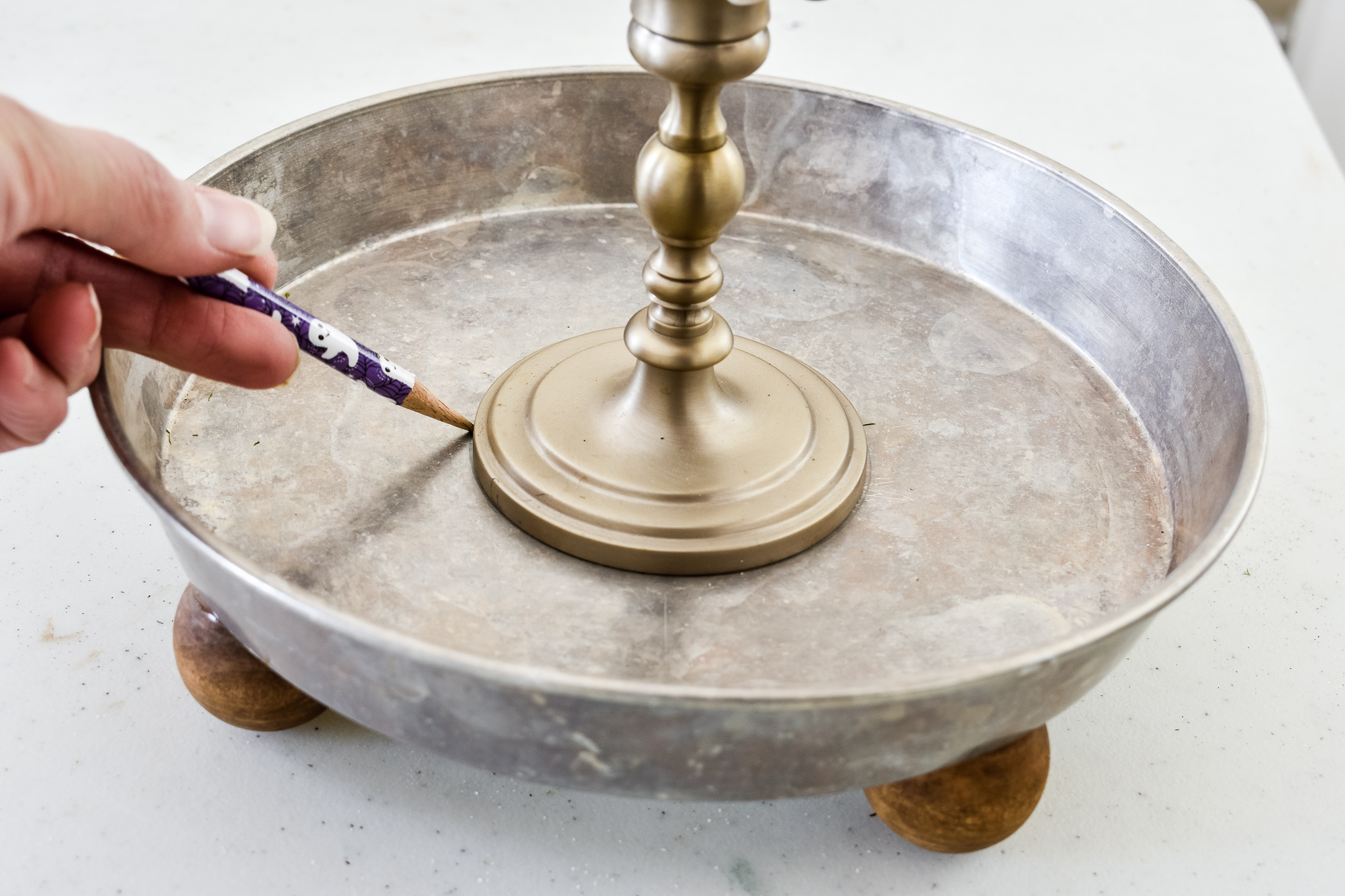 tracing a candlestick with a pencil around  the middle of a cake pan