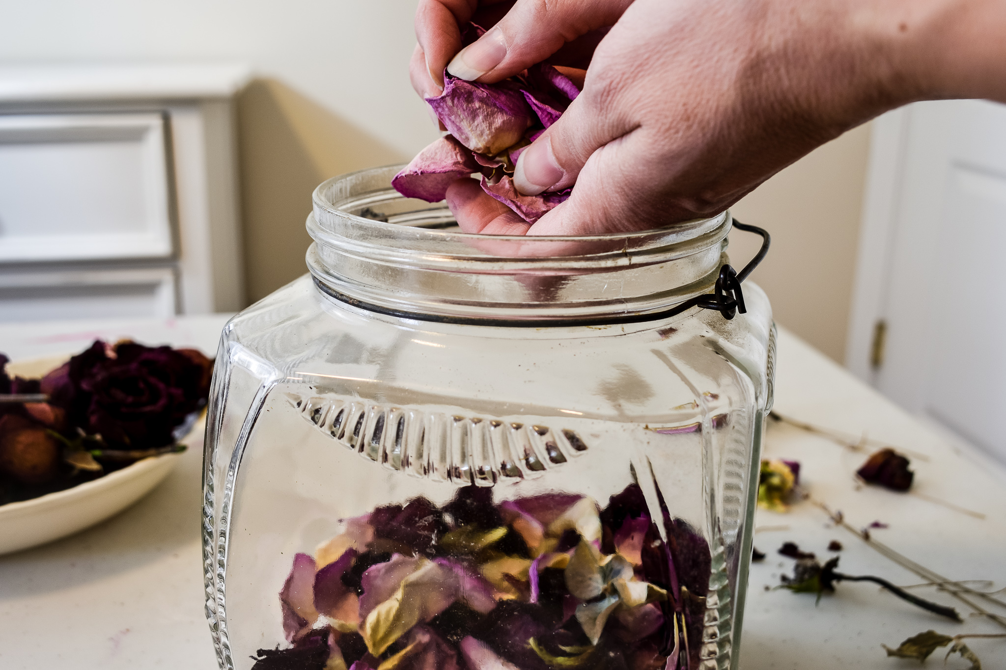 putting dried rose petals into a jar