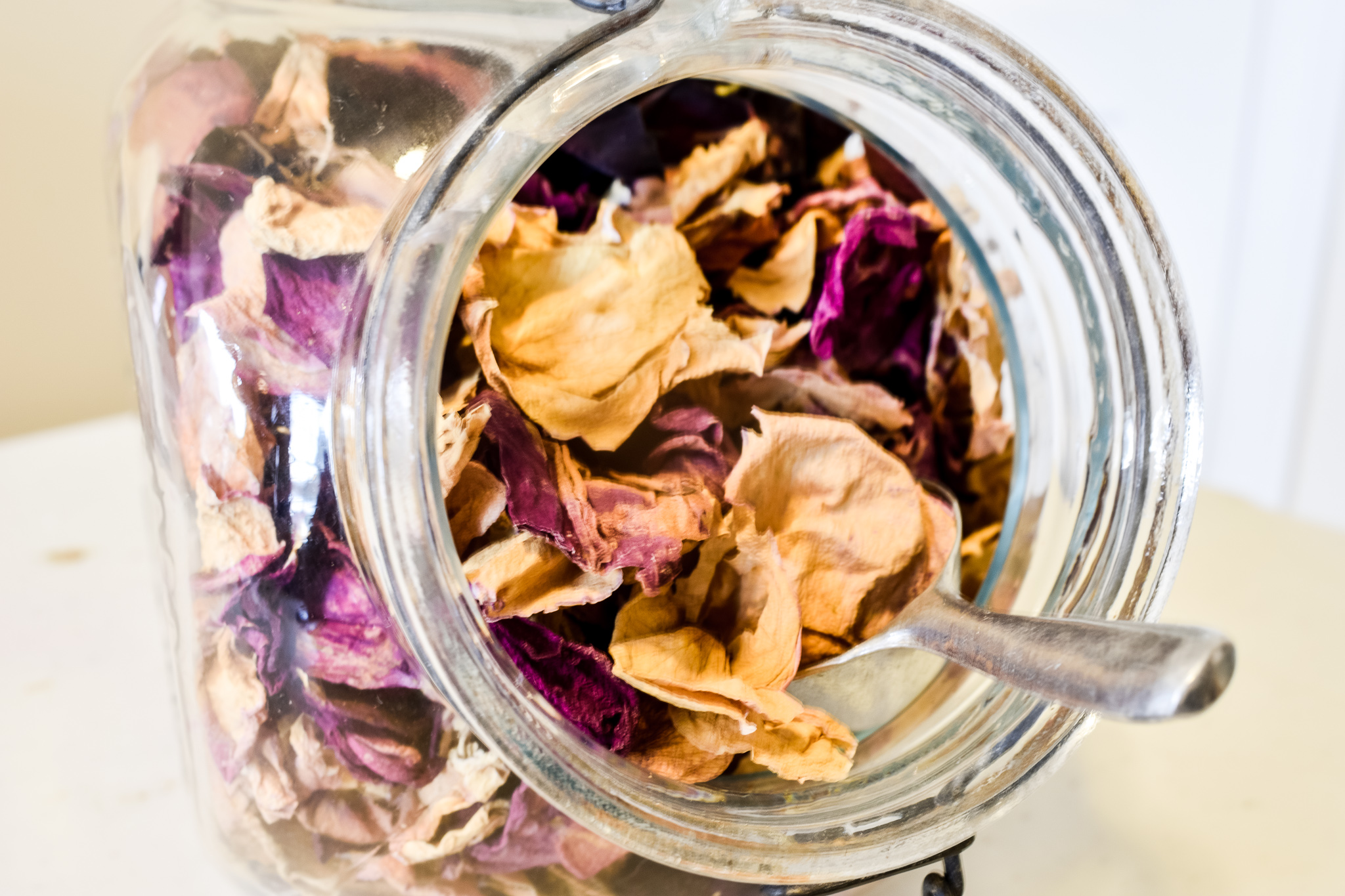 Scooping out rose petals in a vintage glass jar