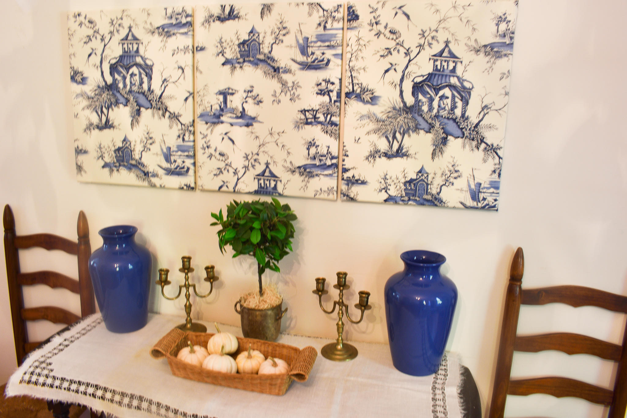 Blue and white toile fabric canvas wall art displayed above a console table