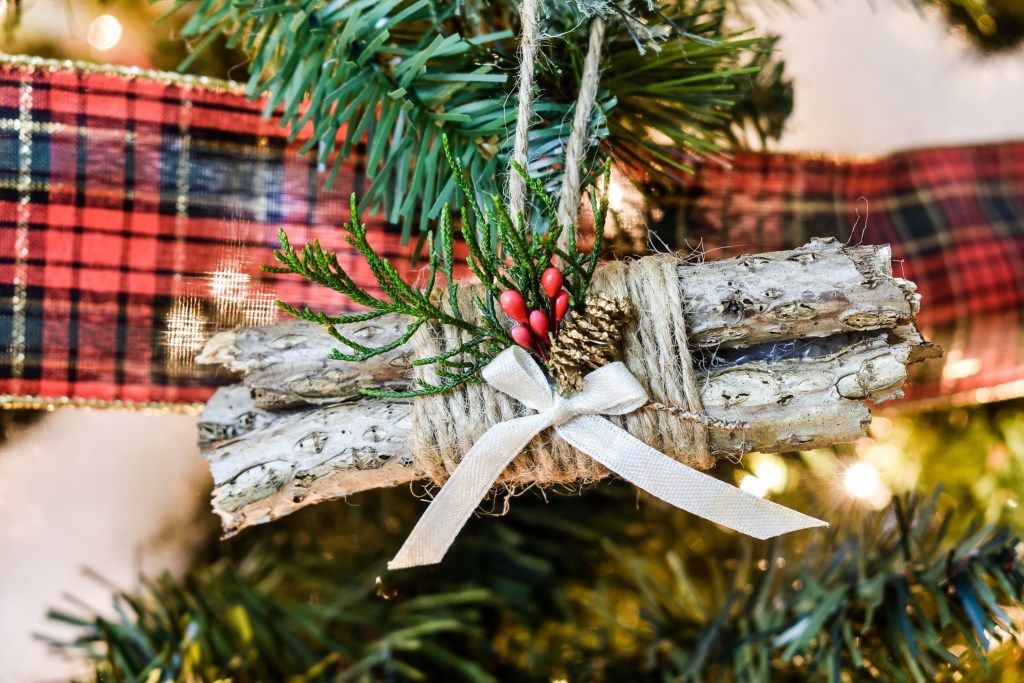 twig bundle ornament wrapped with jute twine and hanging on a Christmas tree