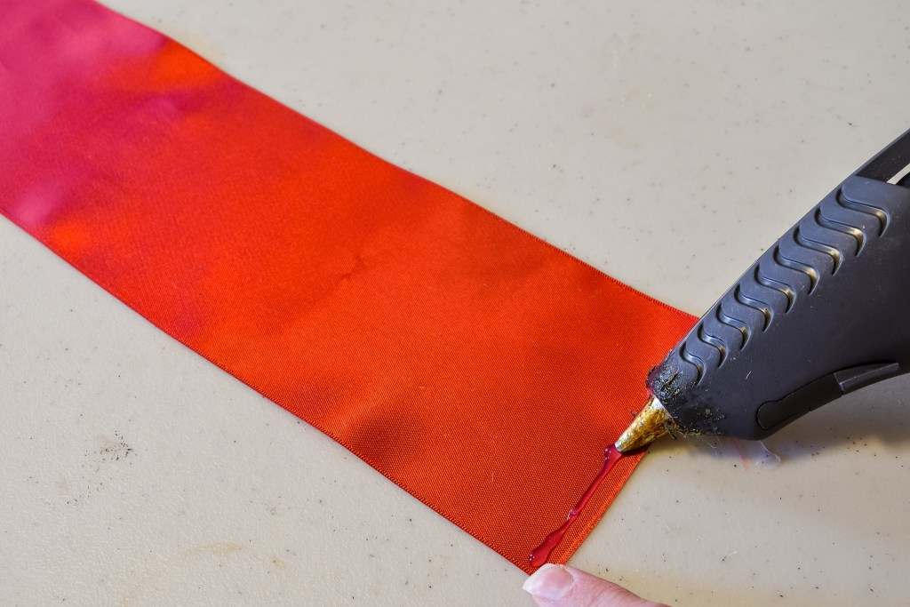 applying hot glue to a red ribbon