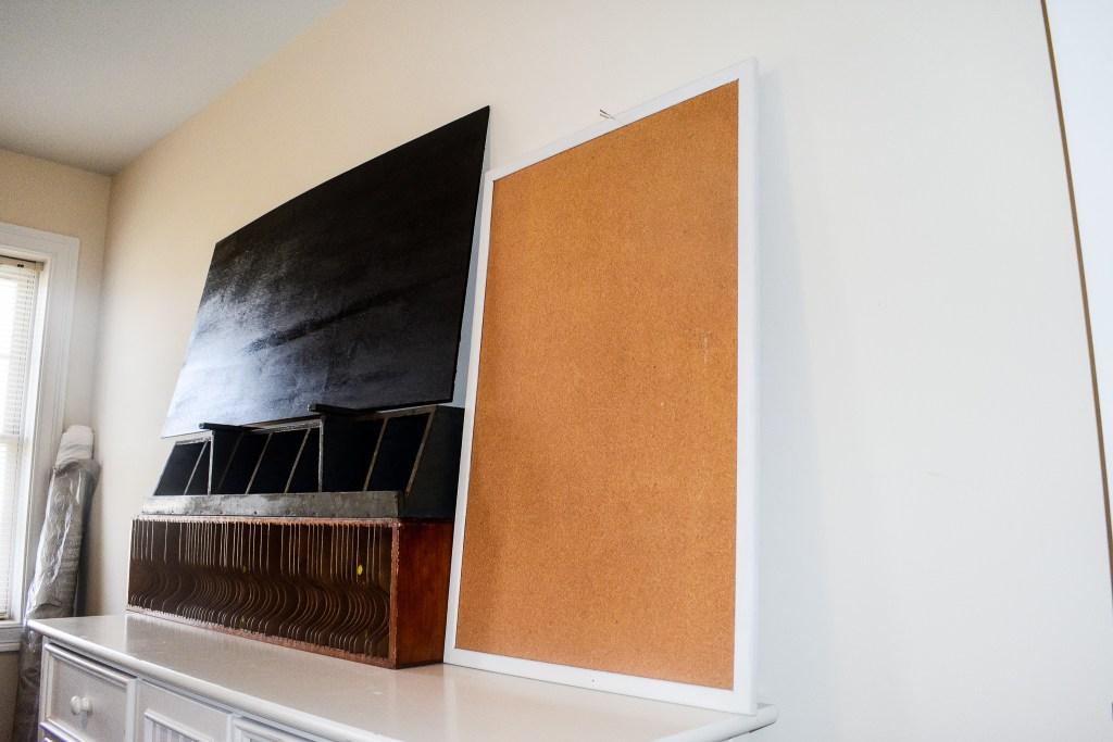 DIY chalkboard, bulletin board, vintage mail sorter and cubbies atop a dresser in a craft room makeover