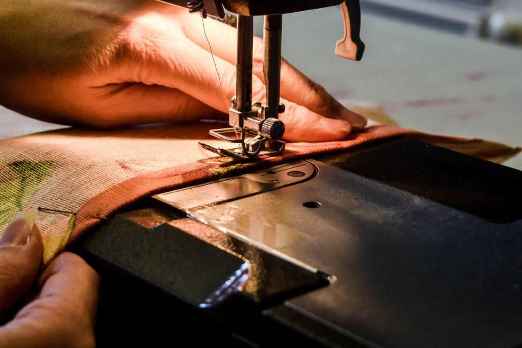 sewing machine stitching a seam on a curtain