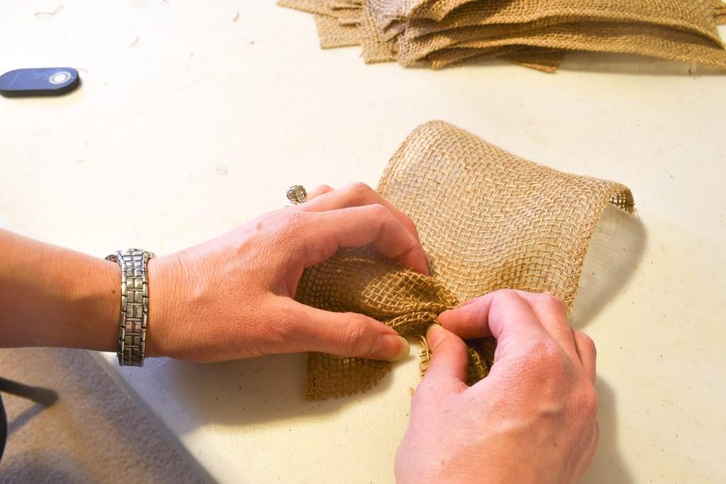 hands scrunching a strip of burlap