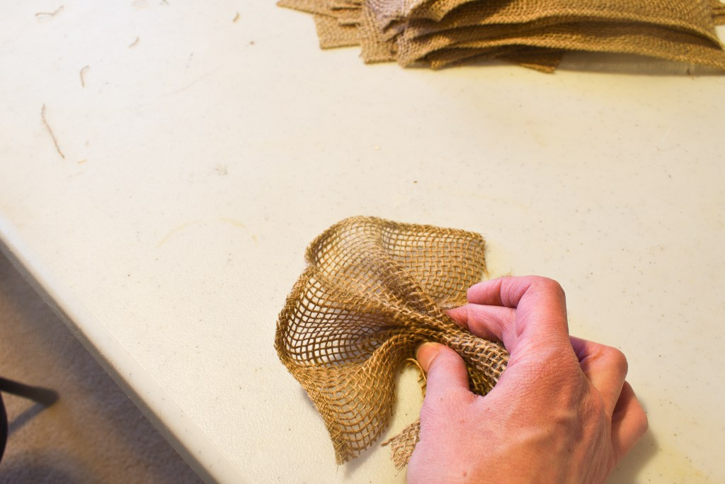 pinching a strip of burlap in the middle with fingers
