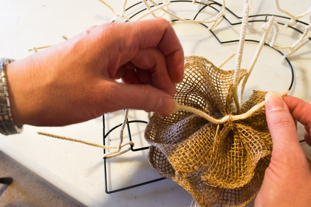 tying a burlap flower to a heart wreath form with pipe cleaners