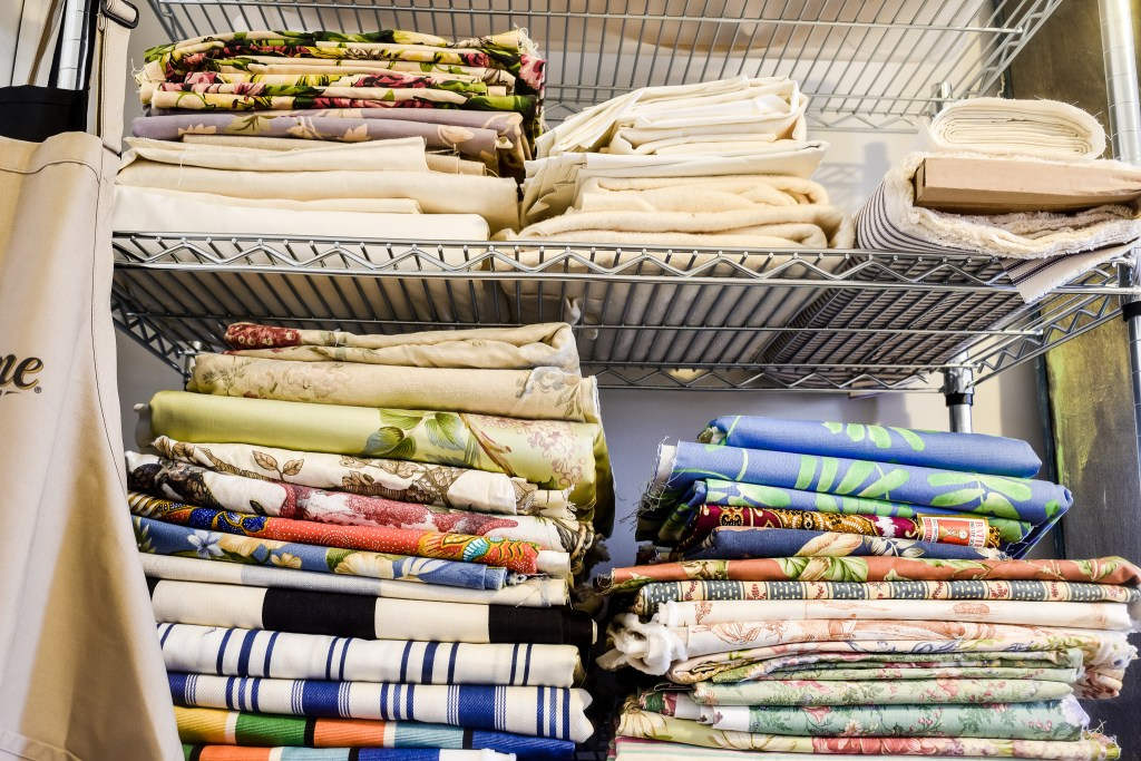 neatly folded stacks of fabric in a craft room reveal