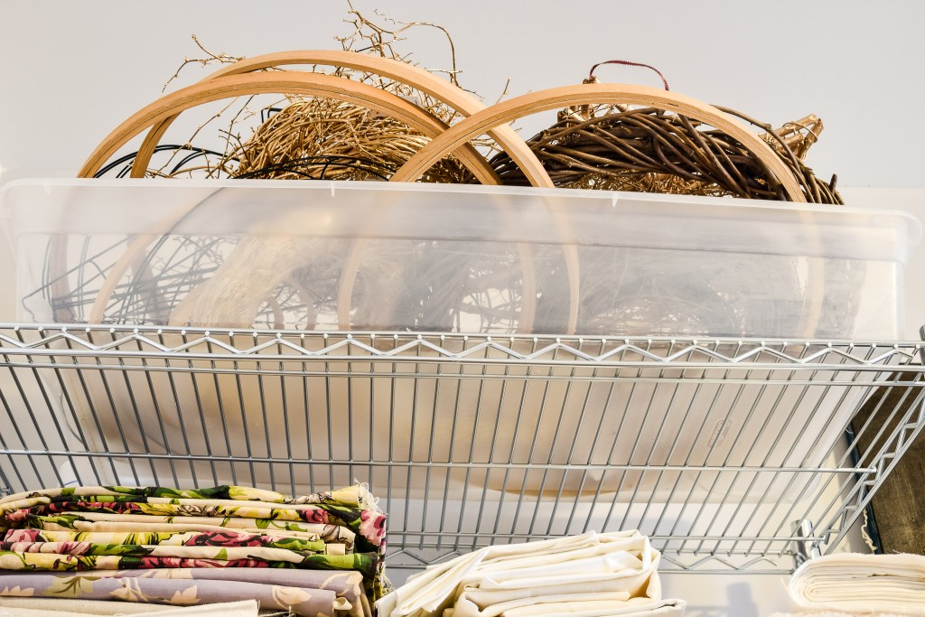 wreath forms in a bin on a shelf in an organized craft room