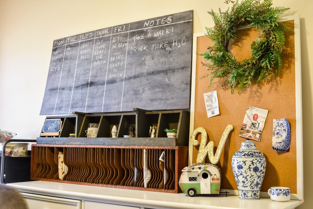 DIY chalk board with weekly to do list and a bulletin board in an organized craft room