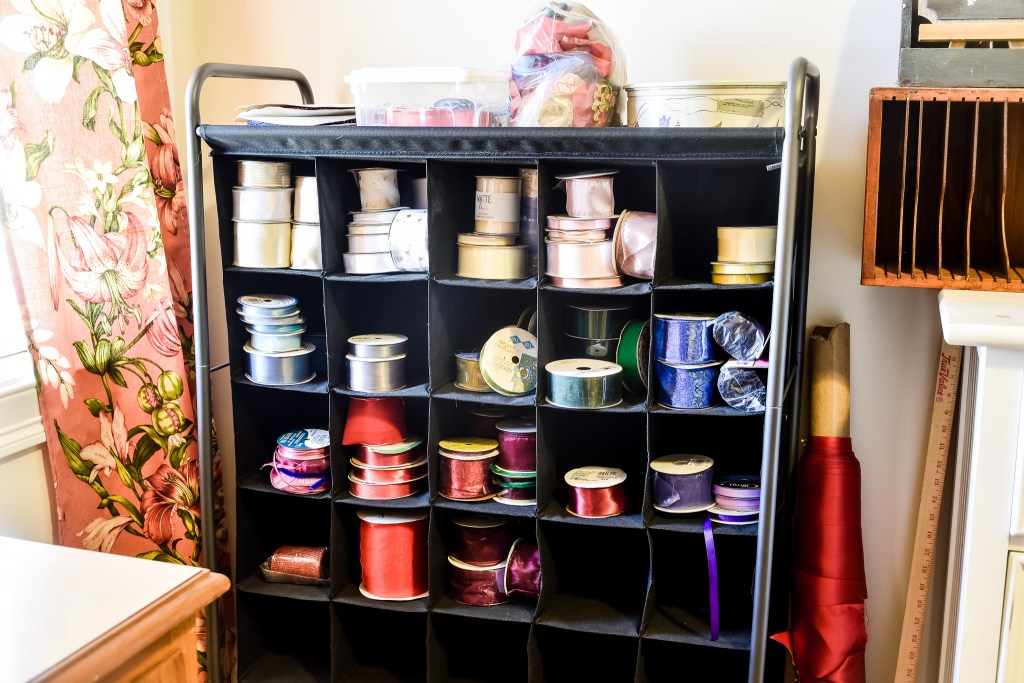 shoe rack being used as ribbon storage in an organized craft room