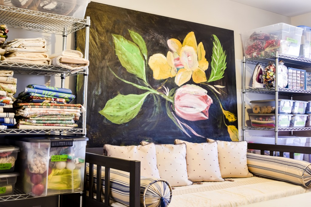 Craft Room Reveal of organized shelves with a daybed and oil painting