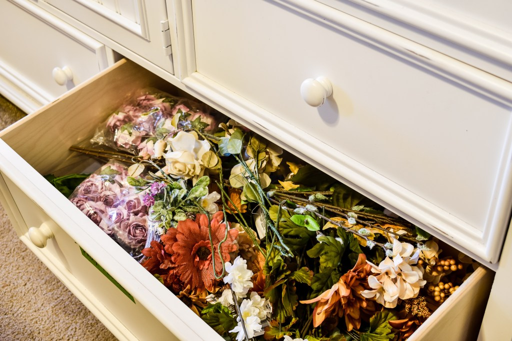 open dresser drawer full of faux florals in an organized craft room