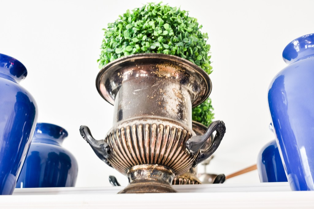 faux boxwood ball inside a tarnished urn on a Spring Mantel