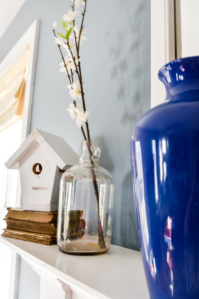 white birdhouse atop a stack of old books beside a vintage jug with a faux flowering branch on a Spring mantel