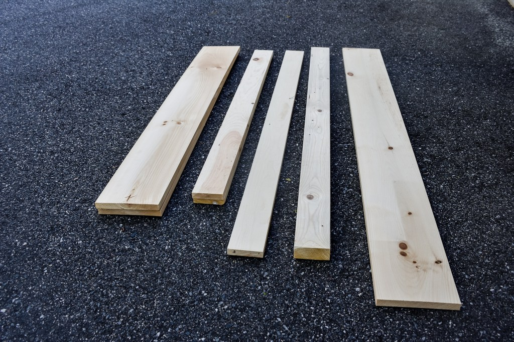raw lumber pieces for DIY faux fireplace and mantel project