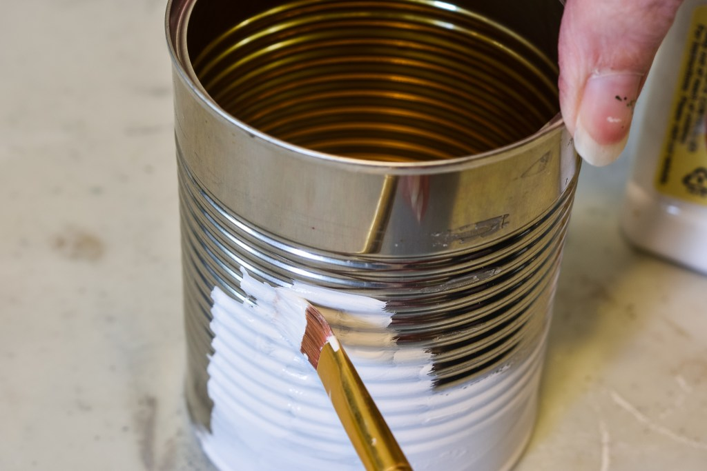applying chalk paint to a diy tin can decor project