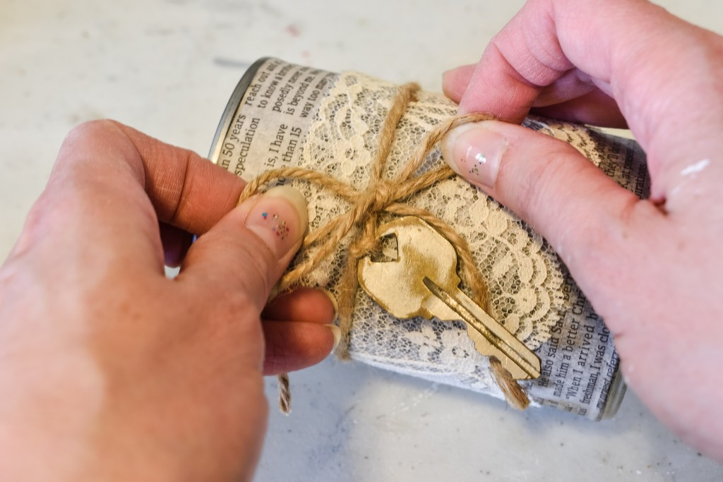 tying a jute twine bow on a book page  diy tin can decor craft project