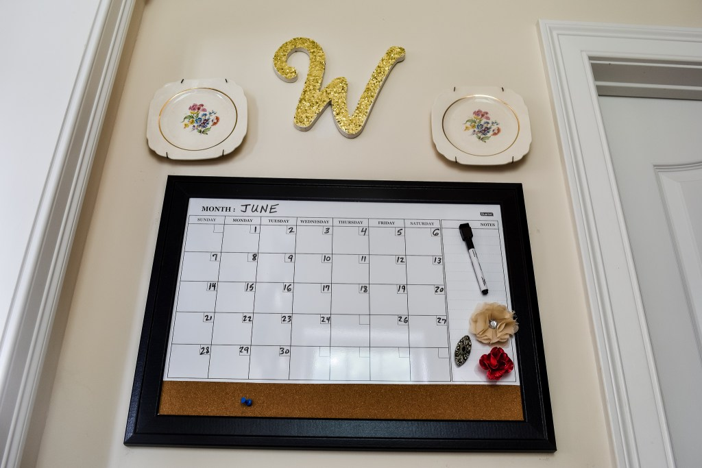 magnetic dry erase calendar with cork board on a small family command center wall