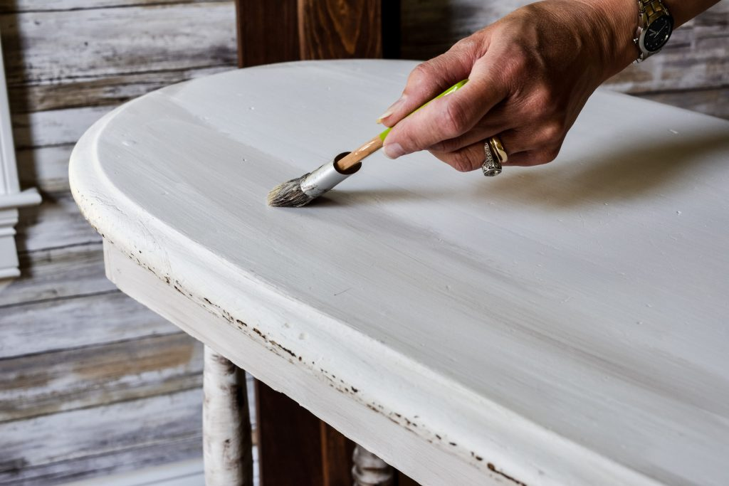 applying dark and clear wax to a side table