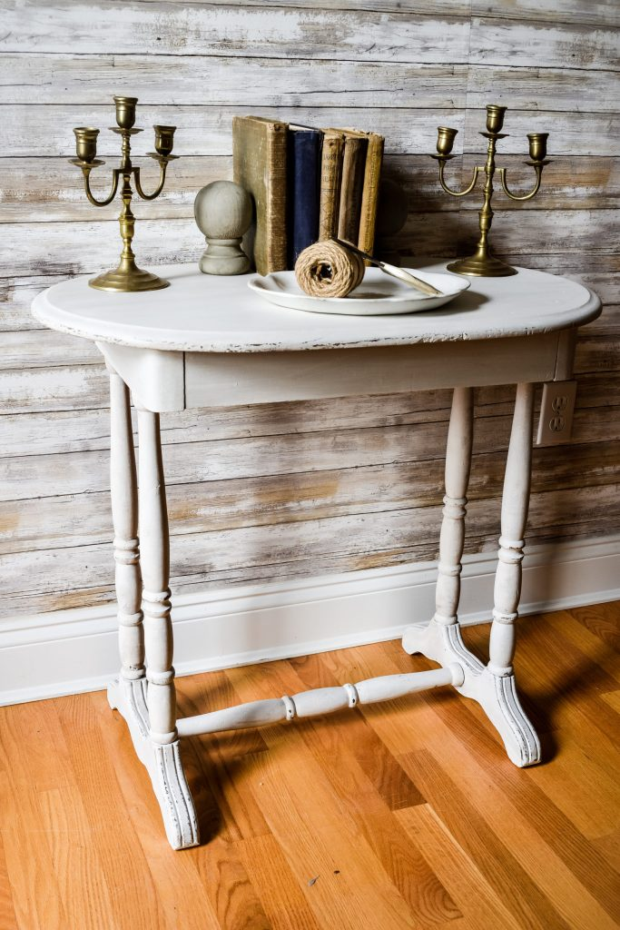 vintage side table painted white and styled with old books and candlesticks