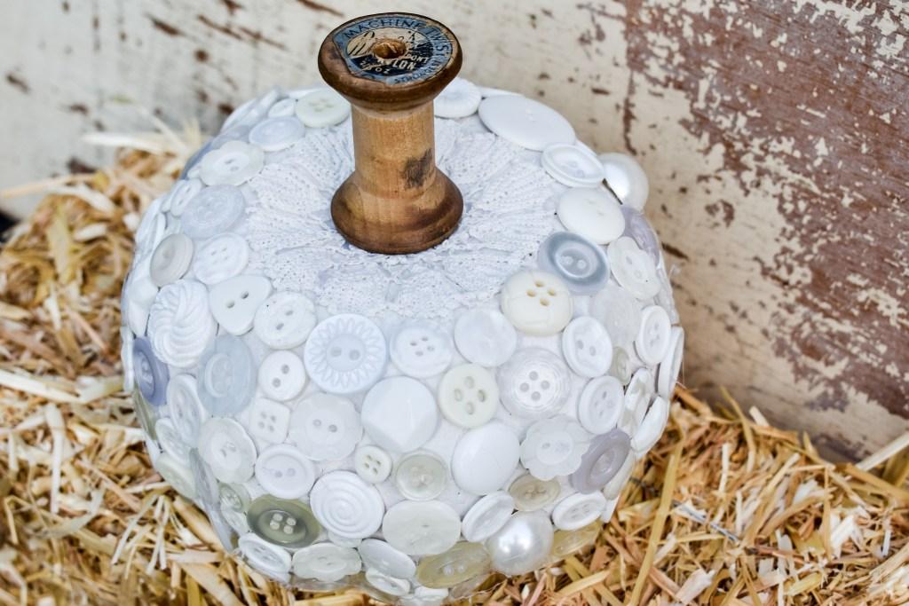 white button pumpkin with a vintage thread spool stem