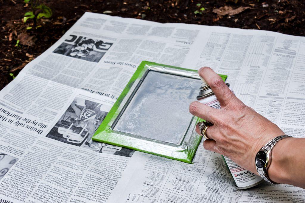 spraying mirror effect spray paint onto a frame