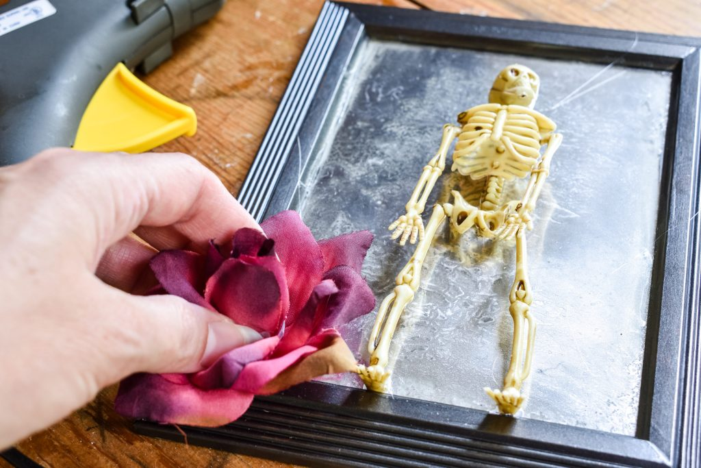 gluing a dark red rose to a frosted skeleton mirror
