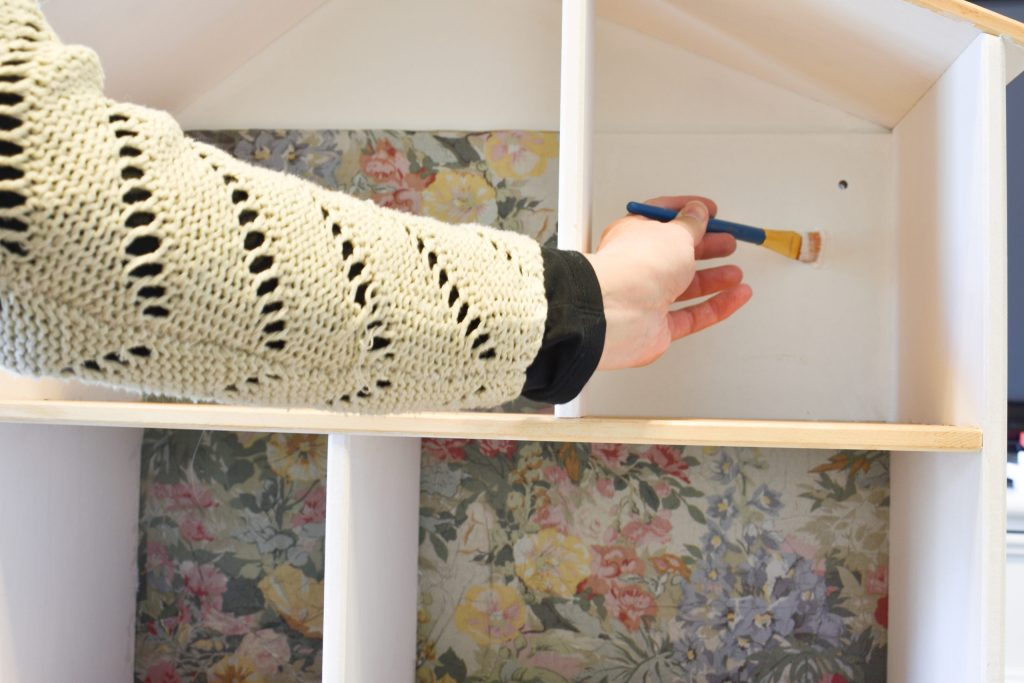 applying mod podge to the walls of the IKEA dollhouse