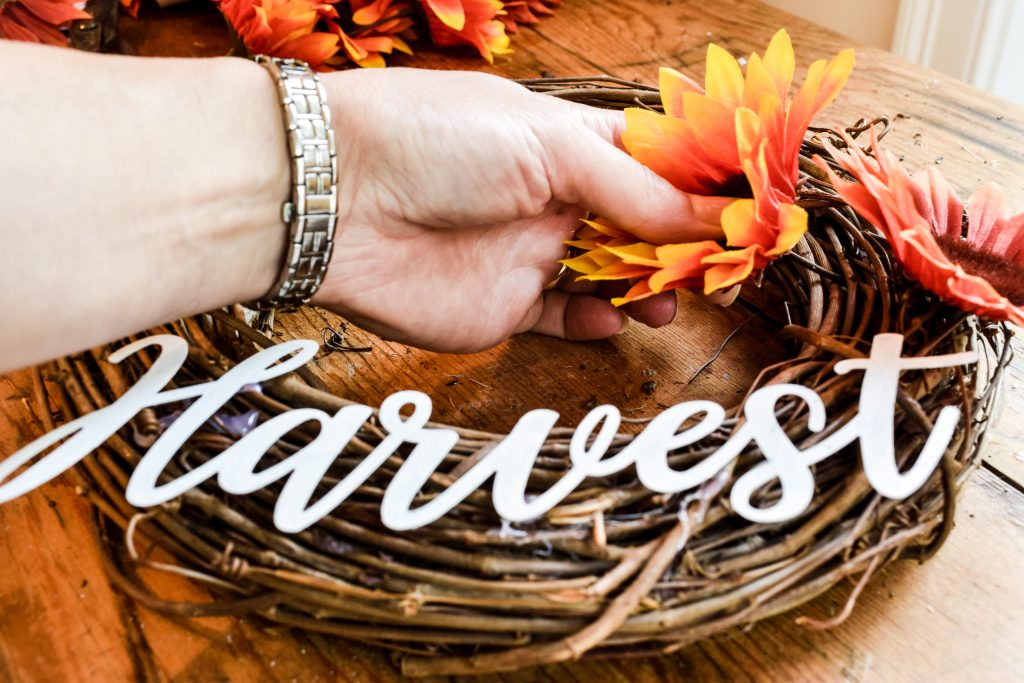 attaching faux Dollar Tree sunflowers to a grapevine fall wreath