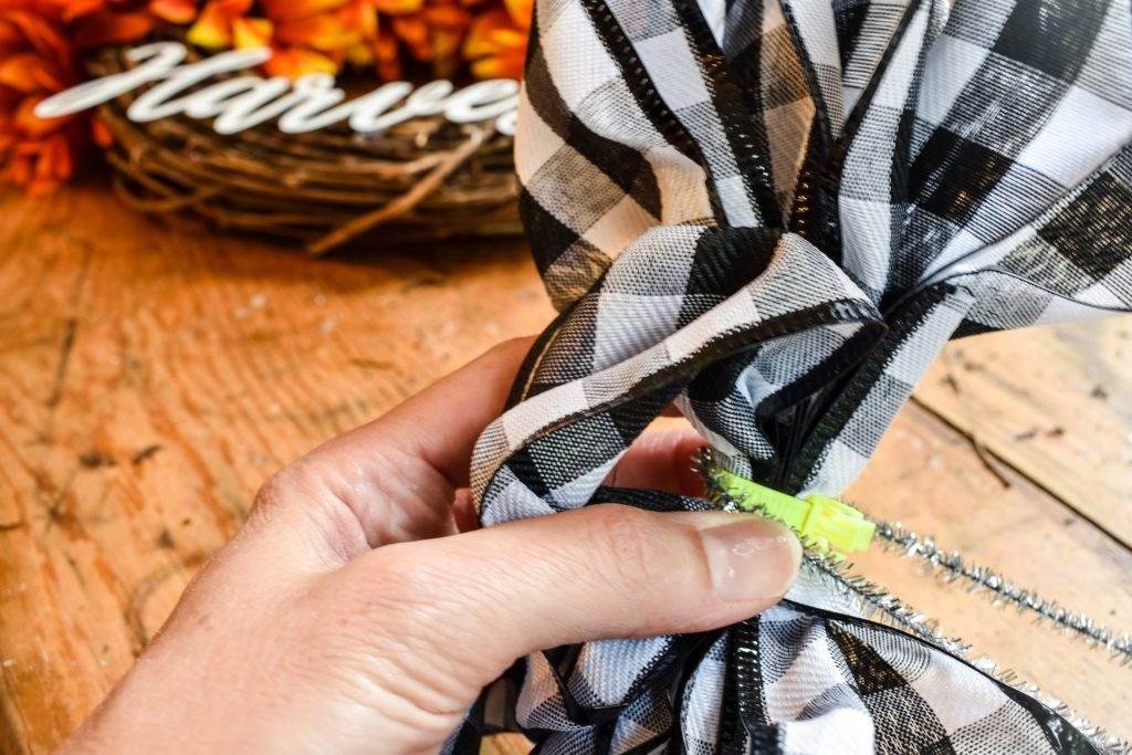 using a pipe cleaner to attach a black and white buffalo check DIY bow to a fall wreath