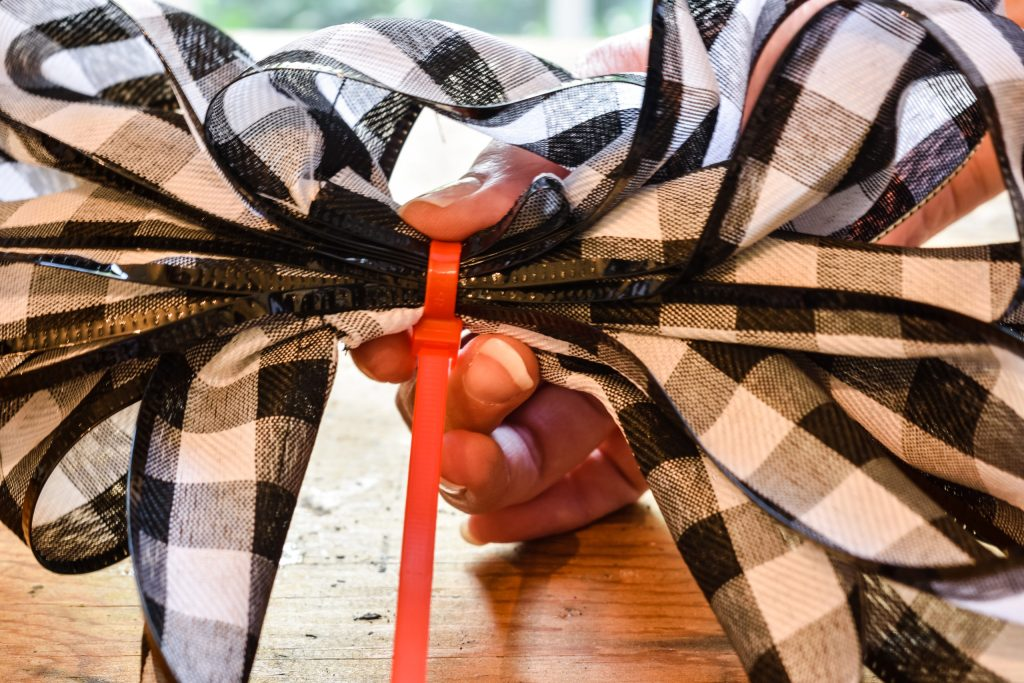 using a zip tie to secure layers of black and white buffalo check ribbon