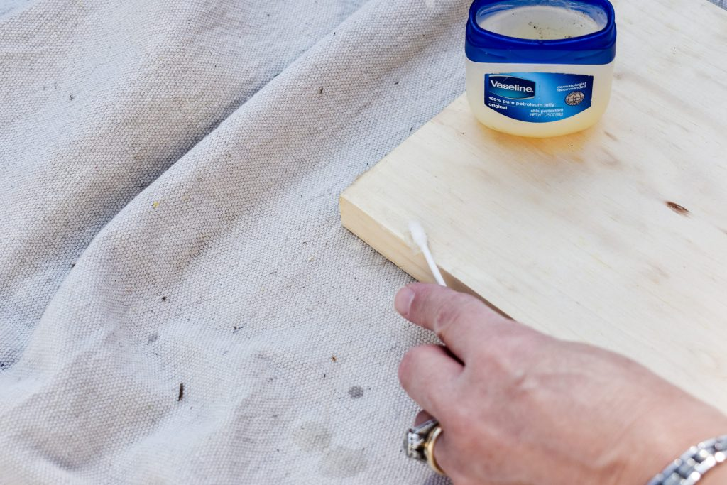 applying vaseline with a Q-tip to a wood board as a paint resist
