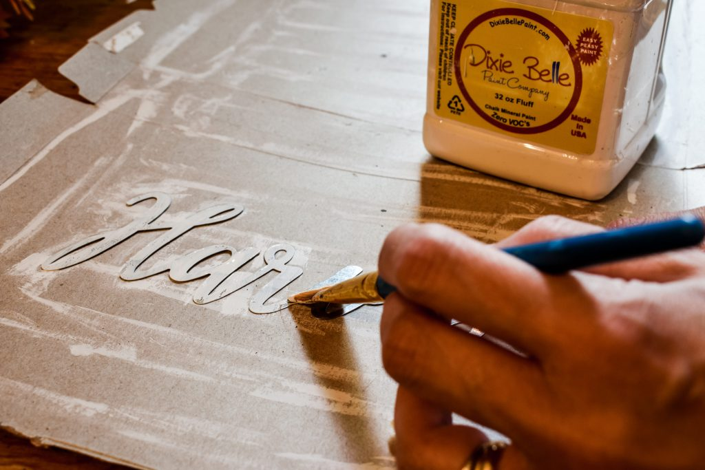 painting a metal Dollar Tree Harvest word cut out with white paint