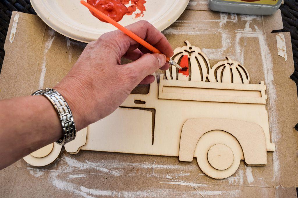 painting a wooden pumpkin truck cutout from Dollar Tree