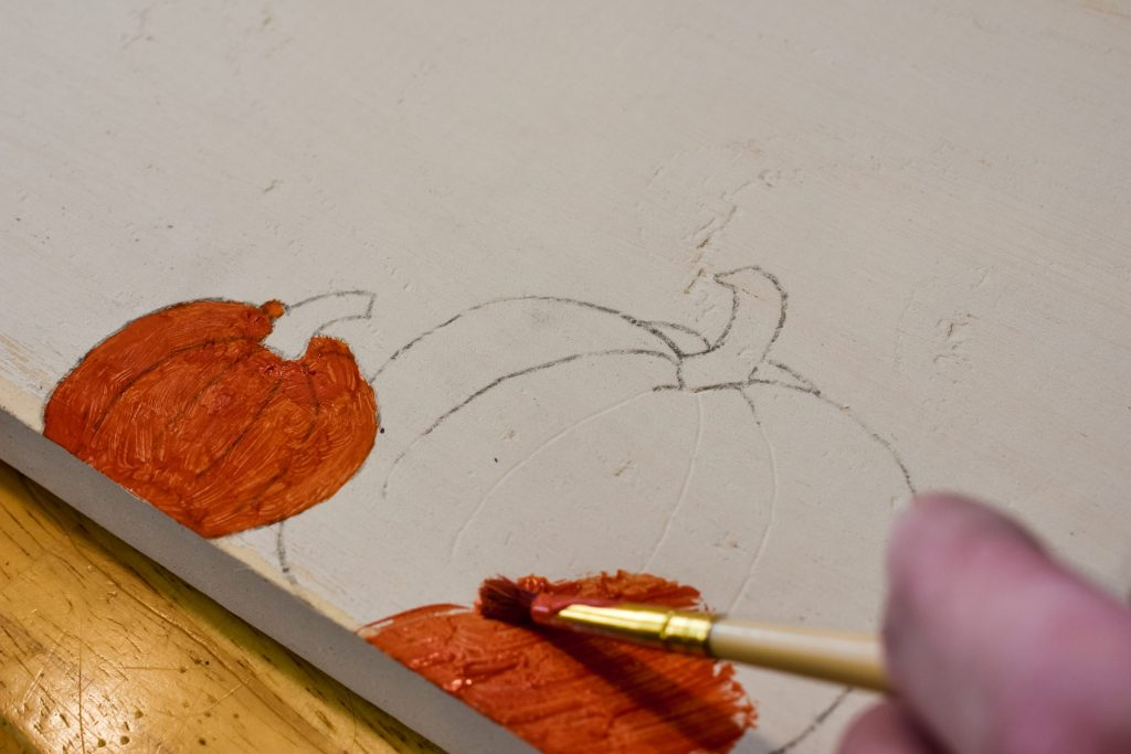 painting pumpkins orange on a painted wooden board used as a sign