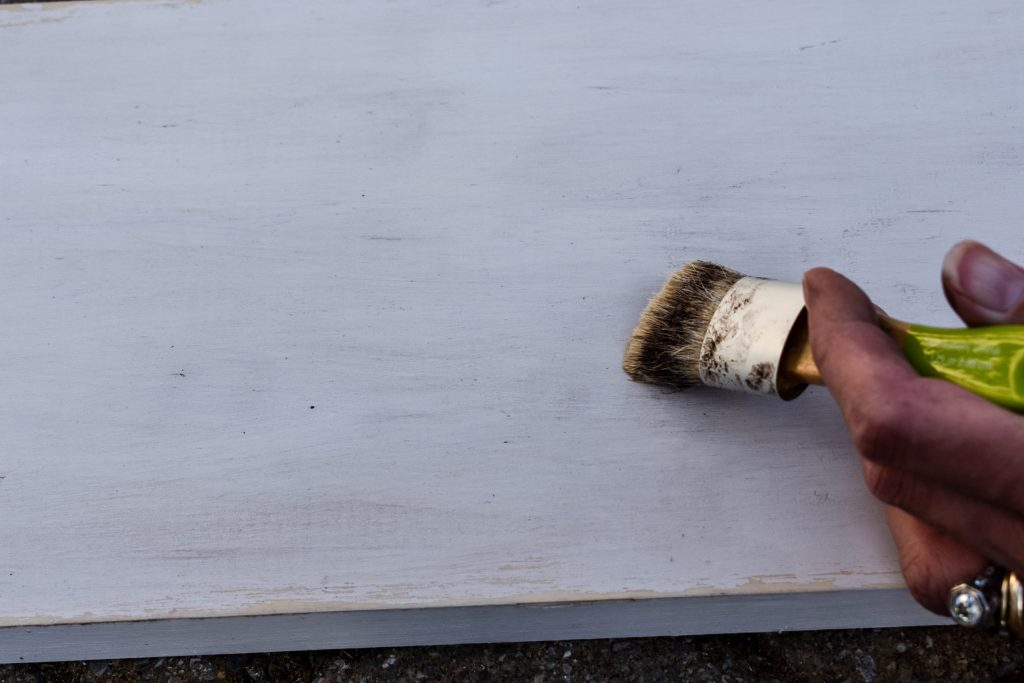 applying brown and clear wax to a board painted white