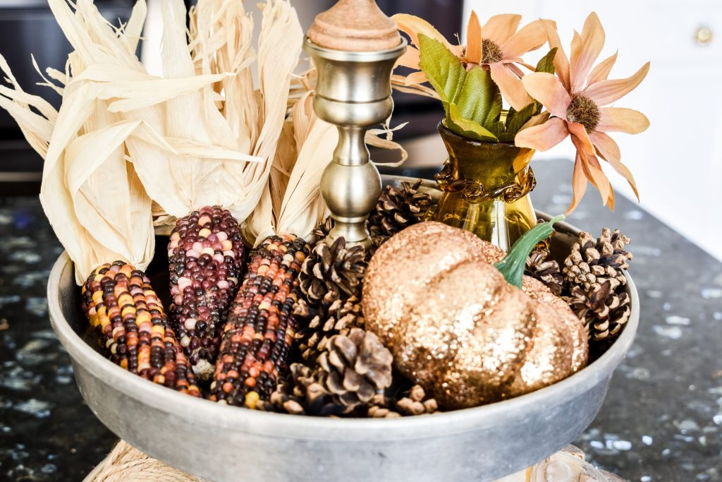Indian corn, pinecones, glitter pumpkin and small amber vase with faux flowers