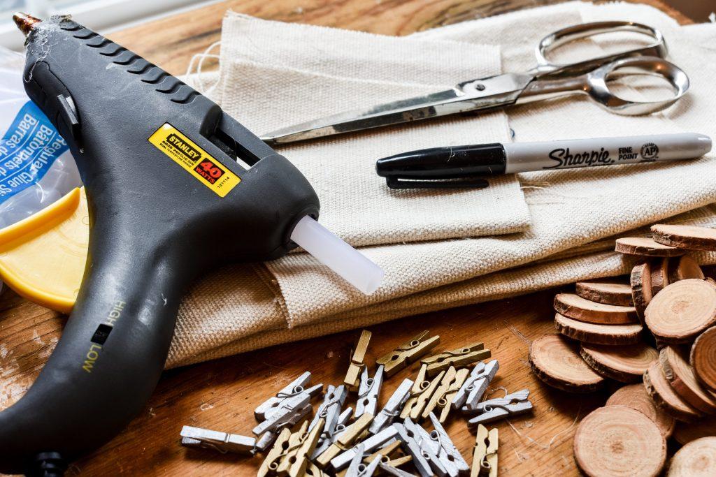 drop cloth, glue gun, sharpie, scissors, wood slices, mini clothespins